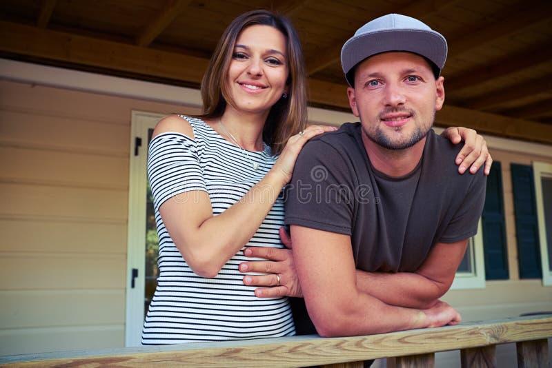 Ungt gift par som poserar på kameran, medan stå på fotografering för bildbyråer