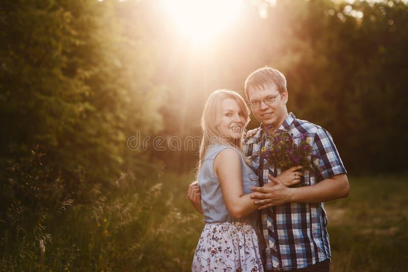 Ungt gift par som utomhus kramar och ser kameran arkivbild