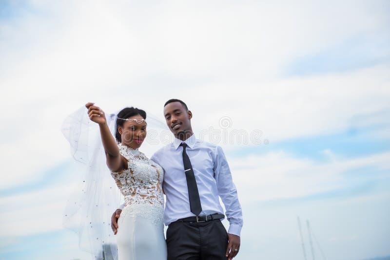 Ungt gift par som utomhus poserar med himmel i bakgrund arkivbilder