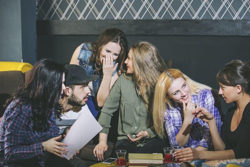 Ungt gladlynt företag av vänner med mobilen, minnestavlan och te Co arkivfoto