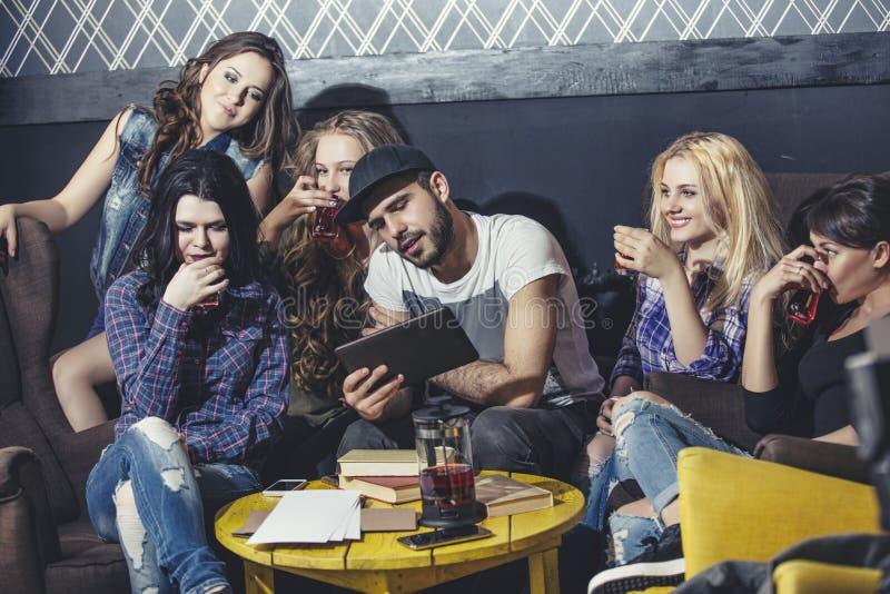 Ungt gladlynt företag av vänner med mobilen, minnestavlan och te Co royaltyfria bilder