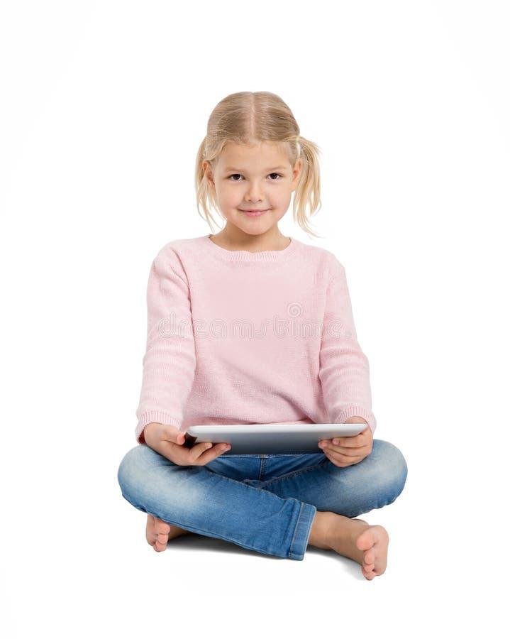 Ungt gladlynt flickasammanträde med den digitala minnestavlan royaltyfri foto