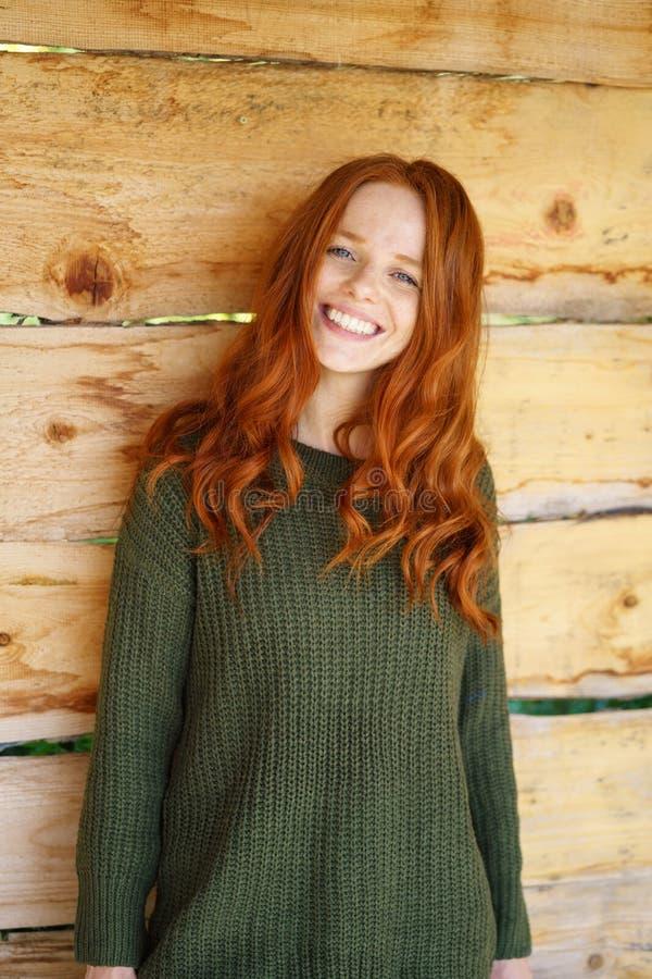 Ungt gladlynt kvinnaanseende mot träväggen arkivfoton