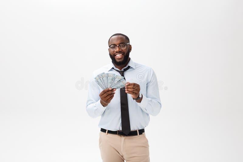 Ungt gladlynt svart affärsmaninnehav och peka på pengar som isoleras på vit royaltyfri foto