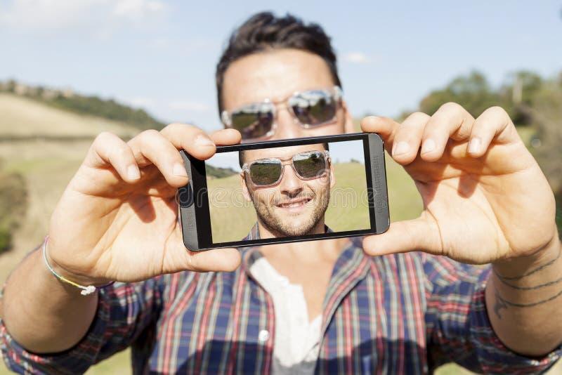 Ungt gulligt vuxet tar en selfie fotografering för bildbyråer