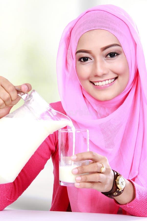 Ungt hälla för muslimkvinna mjölkar in i ett exponeringsglas royaltyfri fotografi