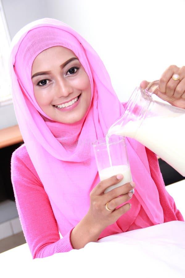 Ungt hälla för muslimkvinna mjölkar in i ett exponeringsglas royaltyfria bilder