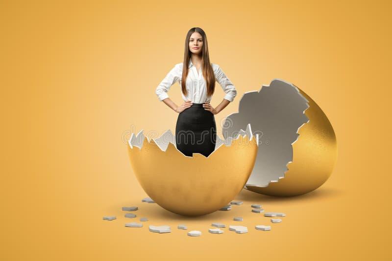 Ungt härligt affärskvinnaanseende med händer på höfter i halvan skal av guld- ägg ut ur som henne som kläckas precis royaltyfria bilder