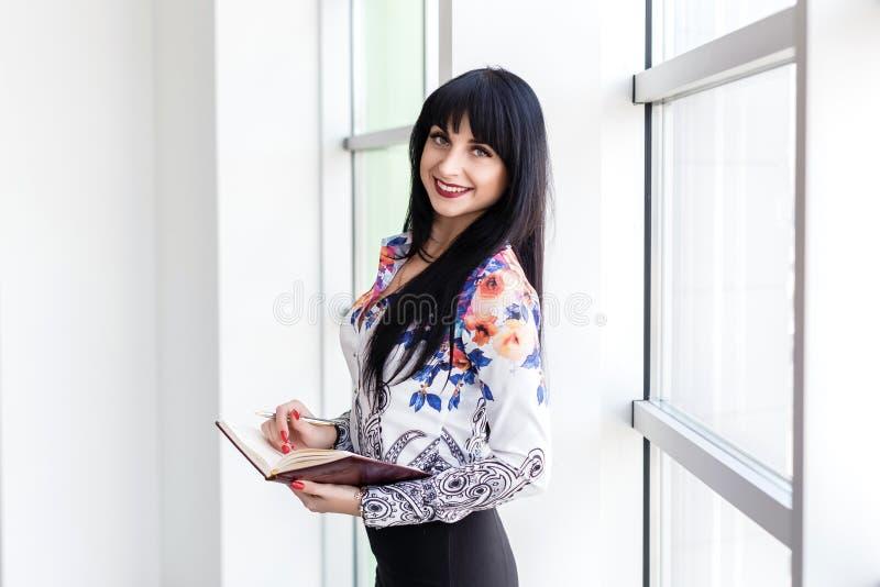Ungt härligt affärskvinnaanseende nära fönster och att skriva i en anteckningsbok som ser le för kamera fotografering för bildbyråer