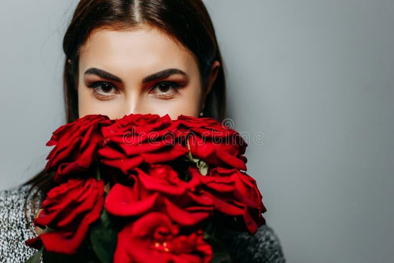 Ungt härligt attraktivt kvinnanederlag bak röda rosor Flicka w royaltyfri bild