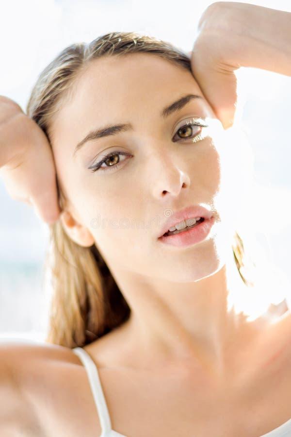Ungt härligt blont damslut upp med solljus på hennes framsida royaltyfri fotografi