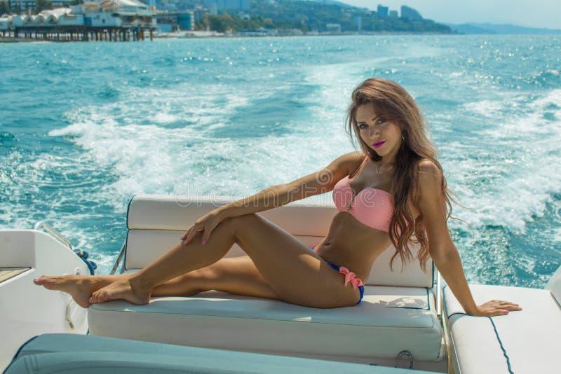Ungt härligt brunettflickasammanträde på den lyxiga yachten i en baddräkt Solbada för flickor långt flickahår royaltyfria bilder