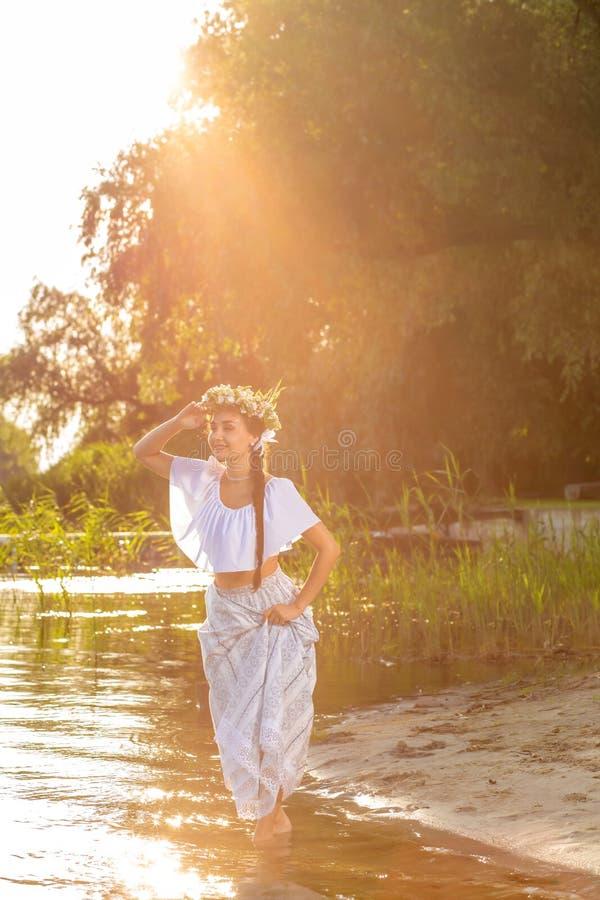 Ungt härligt caucasian kvinnaanseende på banken av floden Traditionell bygdbild med flickan på förgrund arkivfoton