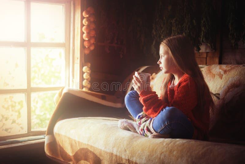 Ungt härligt flickabarn med koppen kaffe arkivbild