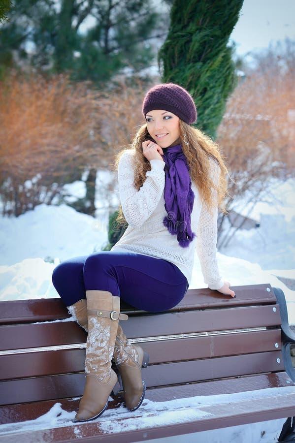 Ungt härligt flickasammanträde på bänken i vinterskog fotografering för bildbyråer