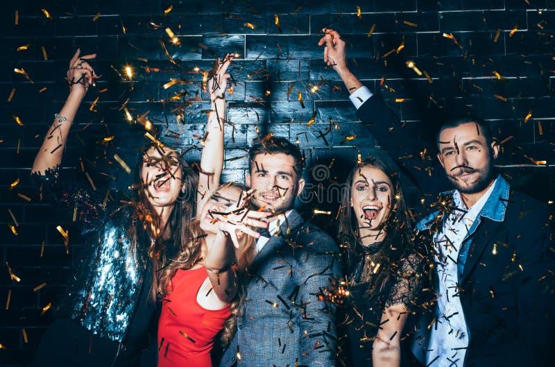 Ungt härligt folk som dansar i konfettier Partigyckel royaltyfri fotografi