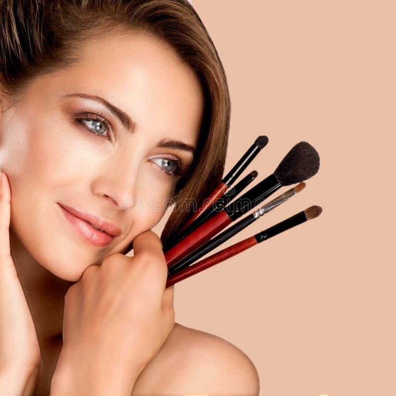 Ungt härligt gör perfekt modellen som applicerar yrkesmässig makeup fotografering för bildbyråer