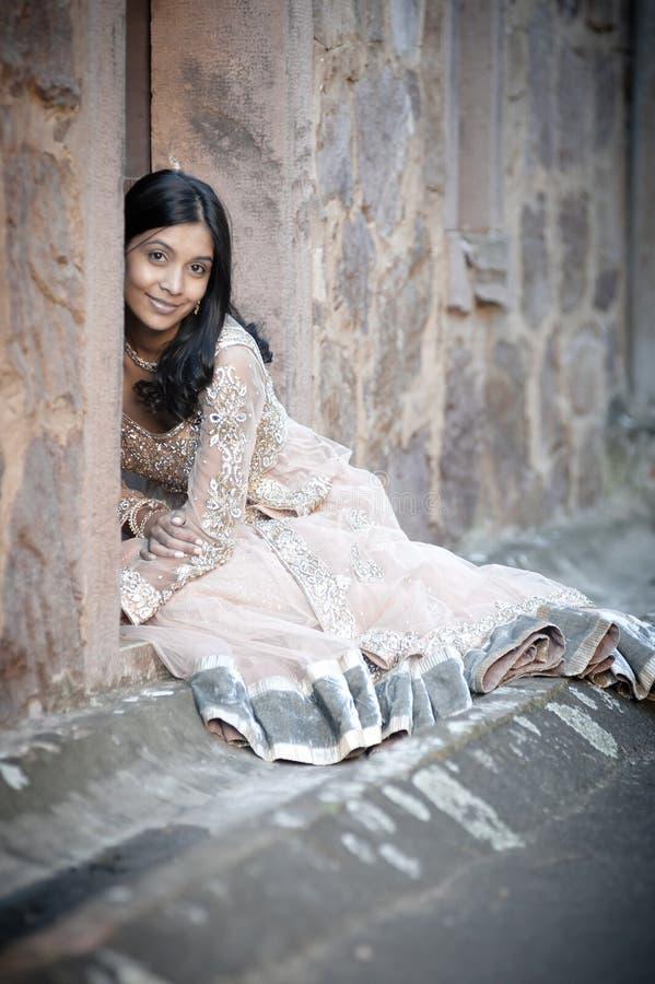 Ungt härligt indiskt kvinnasammanträde mot stenväggen utomhus royaltyfria foton