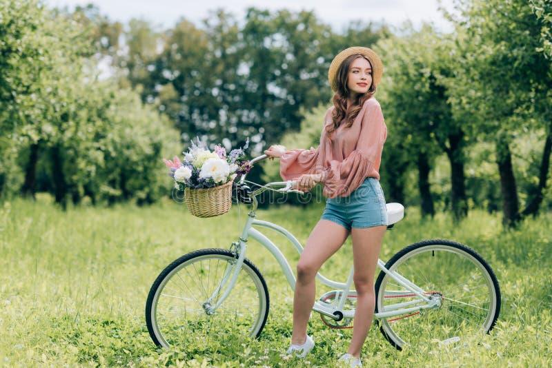 ungt härligt kvinnaanseende nära den retro cykeln med den vide- korgen mycket av blommor royaltyfria bilder