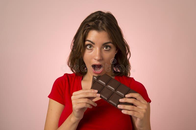 Ungt härligt kvinnainnehav och stickande stor skipp för chokladstång royaltyfri foto