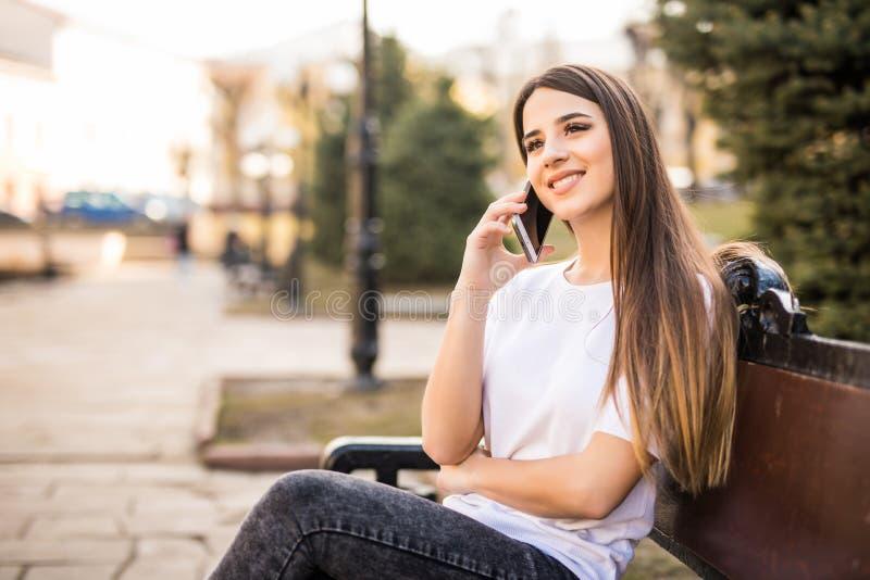 Ungt härligt kvinnasammanträde på en bänk i stadsgatan och tala på telefonen och le fotografering för bildbyråer