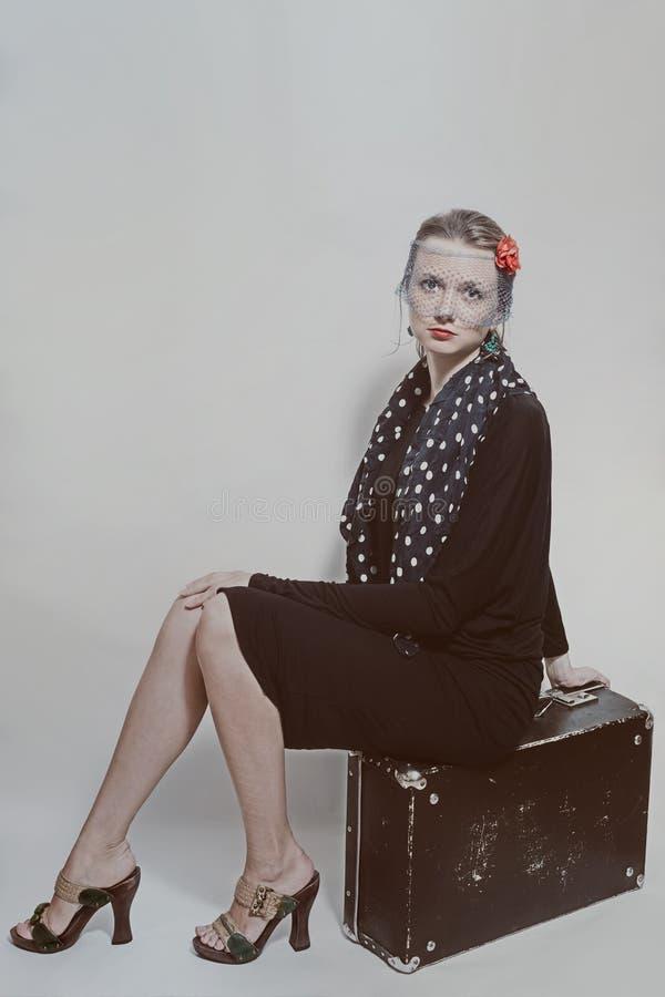 Ungt härligt kvinnasammanträde på en gammal resväska royaltyfri fotografi