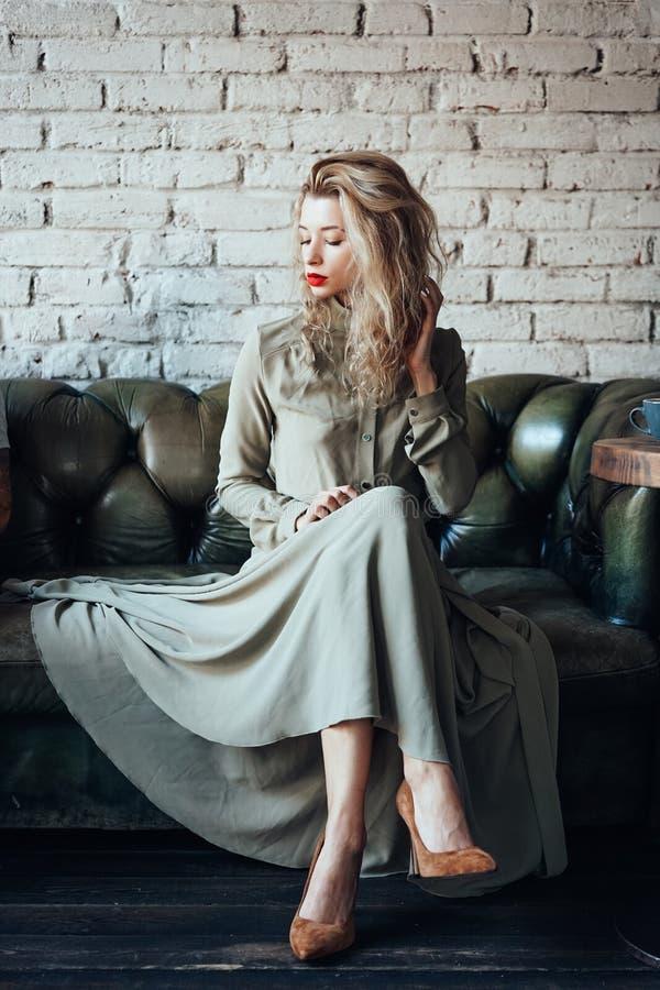 Ungt härligt kvinnasammanträde på en soffa royaltyfri bild