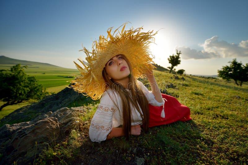 Ungt härligt kvinnasammanträde på fält i sommar fotografering för bildbyråer
