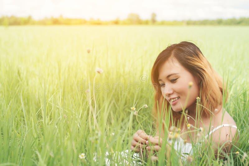 Ungt härligt kvinnasammanträde på grässlätt tycker om naturen och fres arkivfoton
