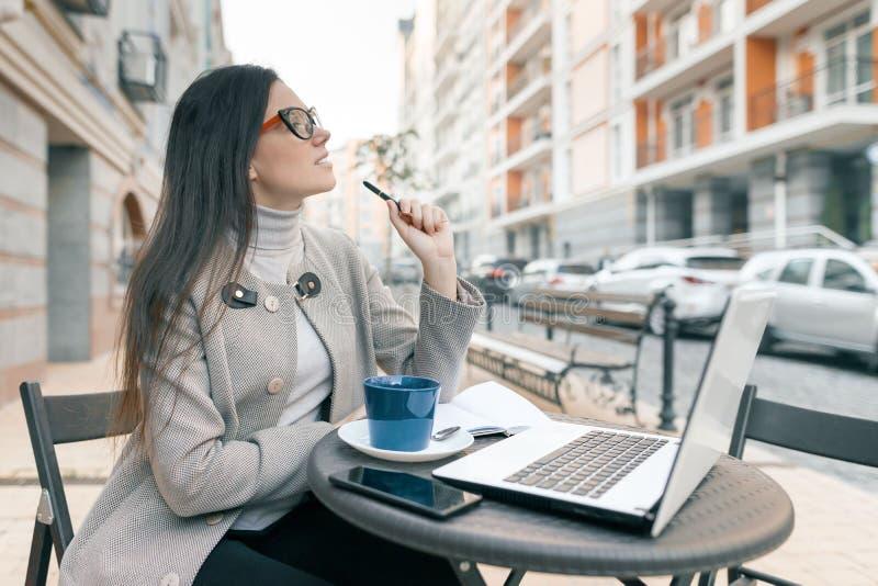 Ungt härligt lag för exponeringsglas för flickastudent som bärande varmt sitter i ett utomhus- kafé med koppen för bärbar datorda arkivfoton