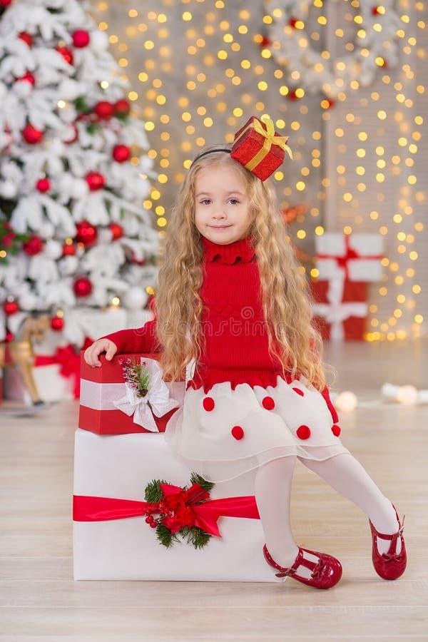 Ungt härligt le för flicka som sitter nära enorma guld- gåvor för spegel på pälsjul, gör grön alldeles vita lyxiga trädgarneringa fotografering för bildbyråer