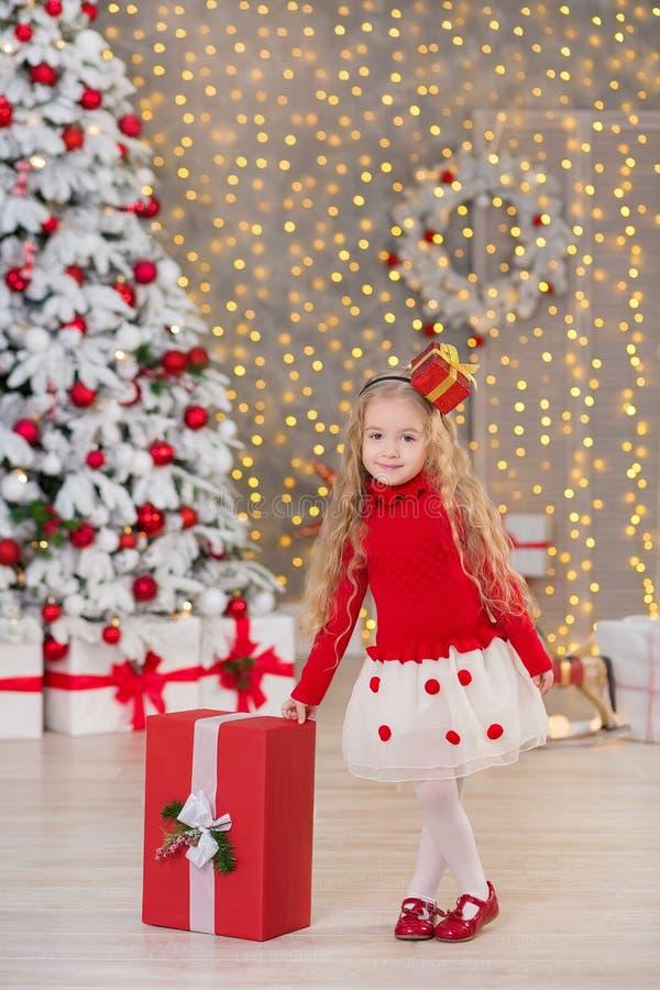 Ungt härligt le för flicka som sitter nära enorma guld- gåvor för spegel på pälsjul, gör grön alldeles vita lyxiga trädgarneringa arkivbild