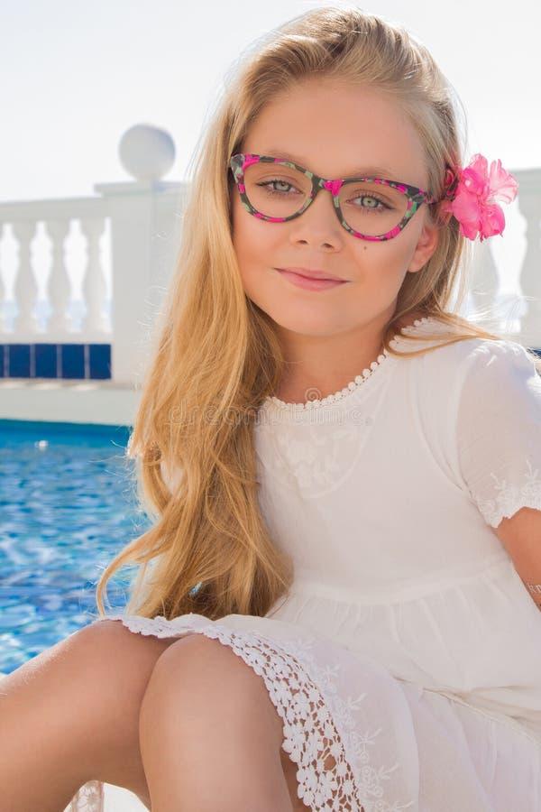 Ungt härligt lockigt blont hår för flickamodellen som länge ler i rosa exponeringsglas och en chic klänning på pölen med räcket o royaltyfri foto
