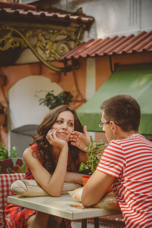 Ungt härligt lyckligt älska parsammanträde på det frilufts- kafét för gata som ser de Början av kärlekshistorien förhållande arkivbilder