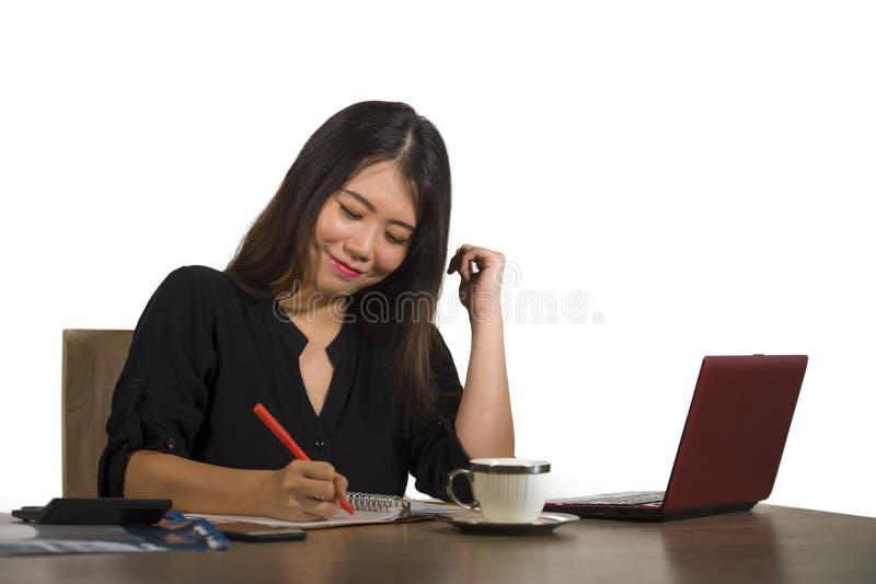Ungt härligt och lyckligt lyckat asiatiskt koreanskt arbeta för affärskvinna kopplade av på skrivbordet för kontorsdatoren som le arkivfoton