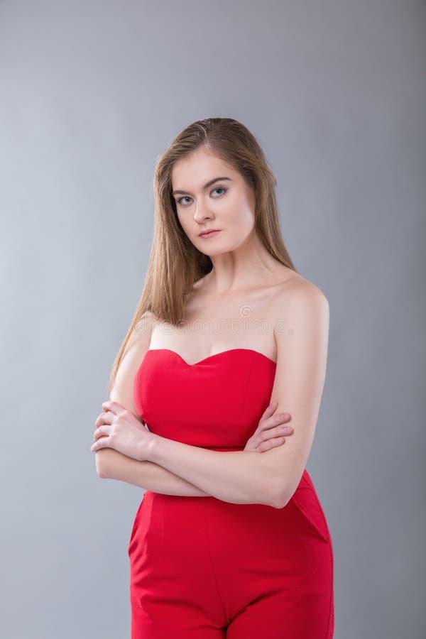 Ungt härligt plus formatmodellen som bär i den röda dräkten, xl-kvinna på grå studiobakgrund royaltyfria bilder