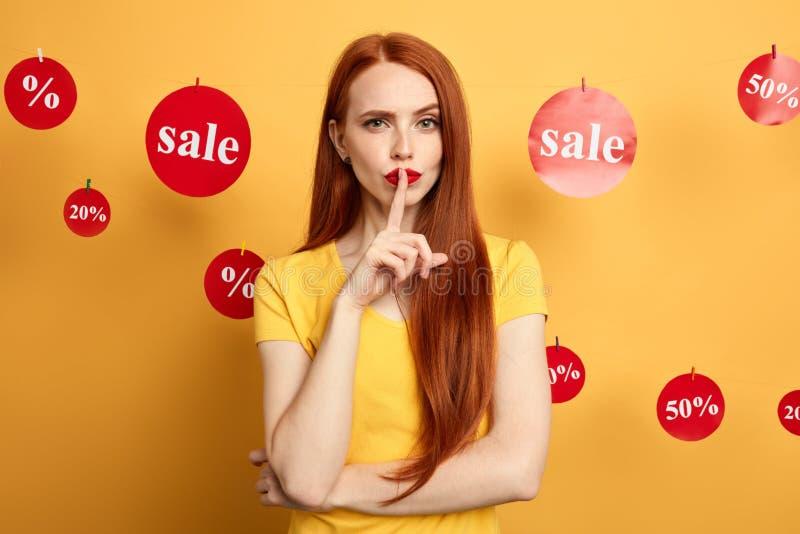 Ungt härligt rödhårigt kvinnainnehavfinger på kanter som visar tystnadgest arkivfoton