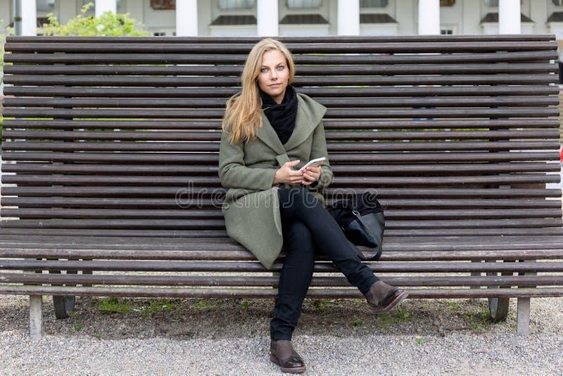 Ungt härligt vänligt kvinnasammanträde på en parkerabänk royaltyfri fotografi