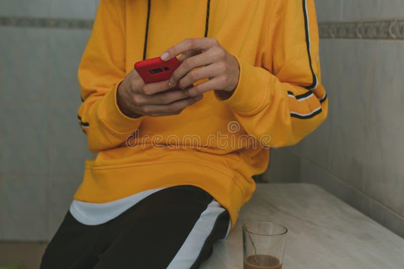 Ungt hemmastatt med mobilen arkivbild