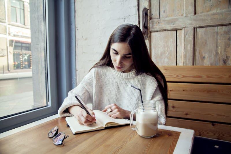 Ungt hipsterflickaarbete i kafé, med anteckningsboken i ett kafé nära fönsterlunchtid med kaffe arkivbild
