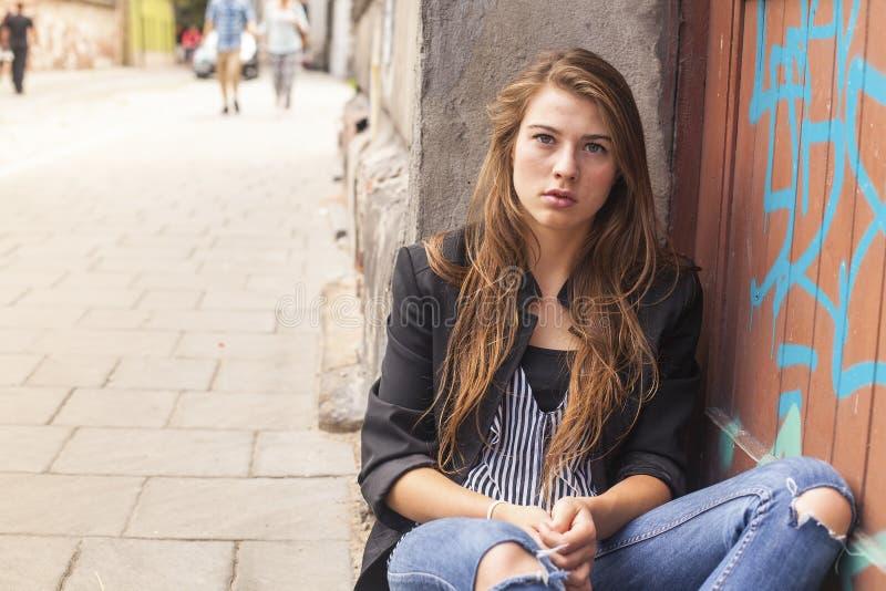 Ungt hipsterflickasammanträde på gatan Problemtonåring arkivbild