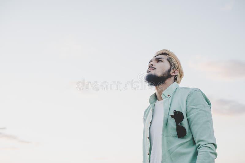 Ungt hipstermananseende i parkera med himmel som bort ser fotografering för bildbyråer