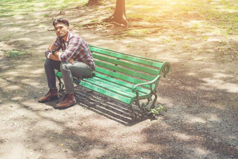 Ungt hipstermansammanträde på en träbänk i parkera royaltyfri bild