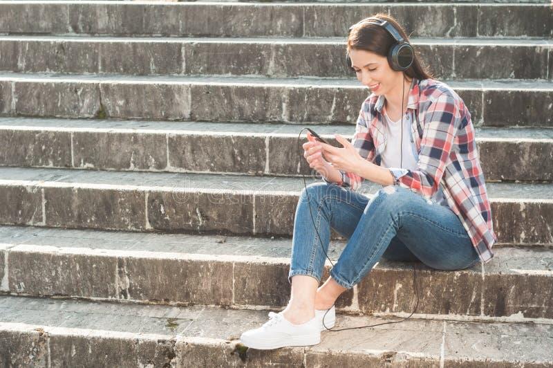 Ungt hipstersammanträde på trappa med smartphonen och hörlurar arkivfoto