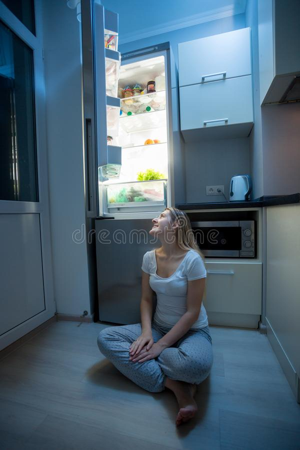 Ungt hungrigt kvinnasammanträde på kökgolv på natten och se på kylen royaltyfria foton
