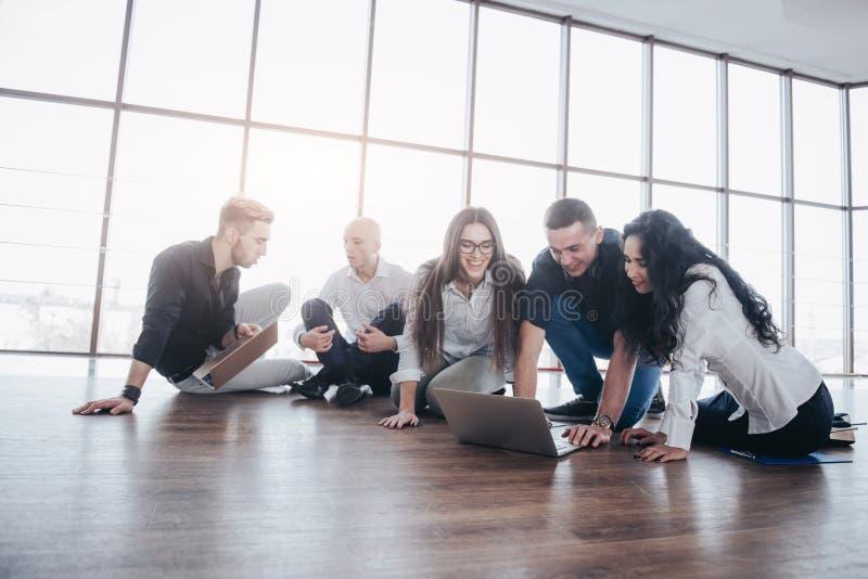 Ungt idérikt folk i modernt kontor Gruppen av ungt affärsfolk arbetar samman med bärbara datorn freelancers royaltyfri fotografi