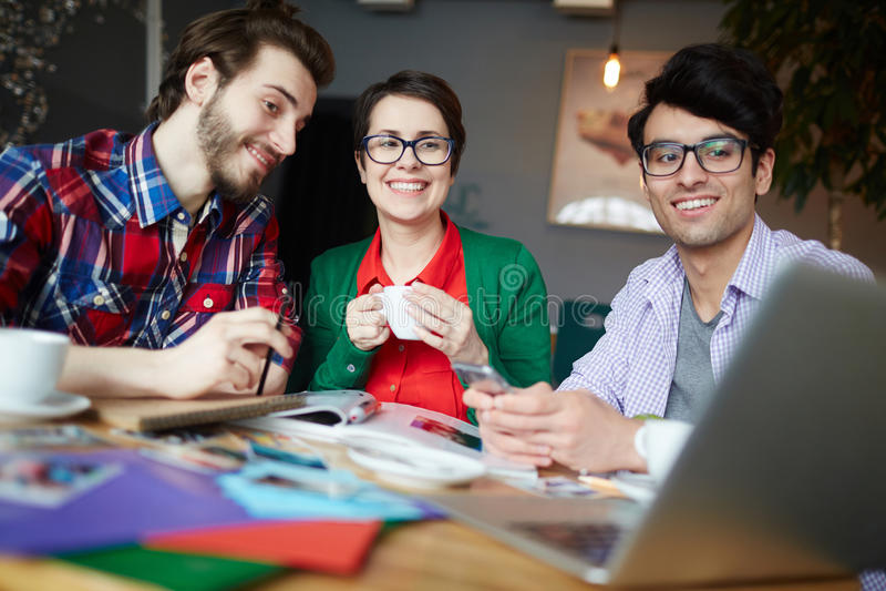 Ungt idérikt folk som ser att le för bärbar datorskärm royaltyfri foto