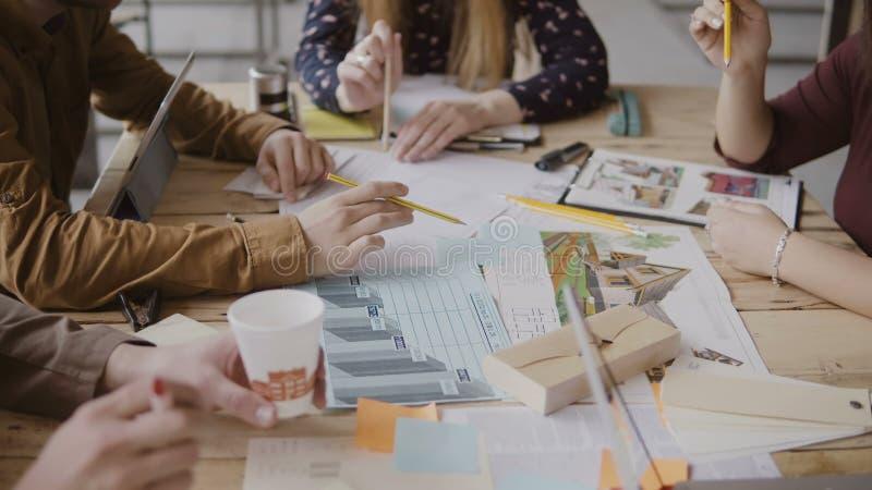 Ungt idérikt lag som arbetar på arkitektoniskt projekt Grupp av folk för blandat lopp som sitter på tabellen och diskuterar fotografering för bildbyråer