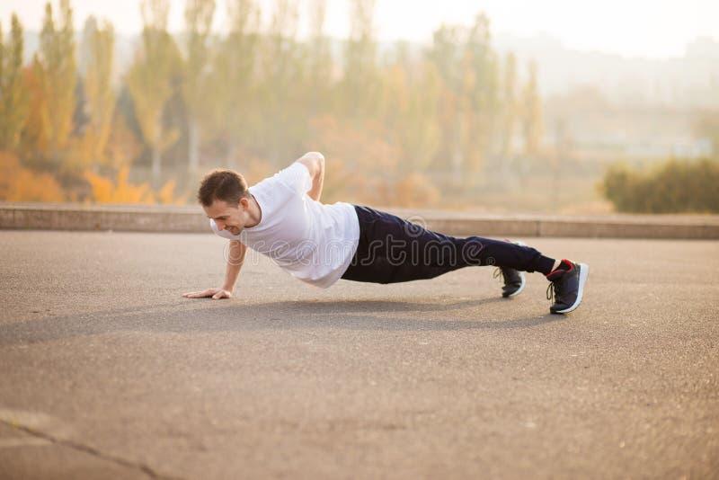 Ungt idrotts- göra för man skjuter upp utomhus idrotts- man Grabb som kopplas in i sportar på naturen arkivfoton