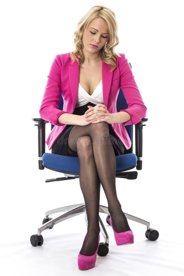 Ungt iklätt rosa sammanträde för affärskvinna på en kontorsstol arkivfoto